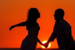 Puesta del sol romántica y siluetas de amantes Imagen de archivo