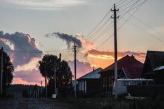 Puesta del sol rosada hermosa de la puesta del sol del verano contra el pueblo del fondo imagen de archivo