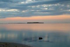 Puesta del sol rosada que refleja en la exposición larga de la playa Fotografía de archivo
