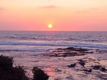Puesta del sol rosada sobre las aguas tranquilas Fotos de archivo libres de regalías