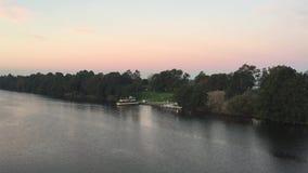 Puesta del sol rosada sobre un río almacen de metraje de vídeo
