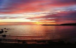 Puesta del sol rosada y amarilla brillante sobre el mar Foto de archivo