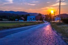 Puesta del sol rural sobre el pequeño pueblo en las montañas Imagenes de archivo