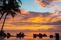 Puesta del sol, sillas de playa, palmeras, silhoue de la piscina del infinito Fotos de archivo