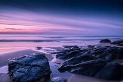 Puesta del sol soñadora de la playa en costa rocosa en la bahía de Watergate, Cornualles, E foto de archivo