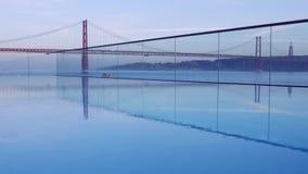 Puesta del sol sobre '25 el puente de abril 'en Lisboa, Portugal con la reflexión de la piscina del infinito almacen de metraje de vídeo