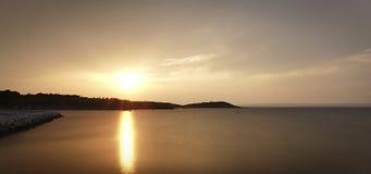 Puesta del sol sobre bahía del mar Fotos de archivo libres de regalías