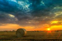 Puesta del sol sobre campo de granja con las balas de heno Fotos de archivo
