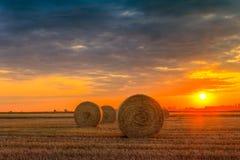 Puesta del sol sobre campo de granja con las balas de heno Imagen de archivo libre de regalías