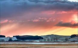 Puesta del sol sobre campo hivernal fotos de archivo libres de regalías