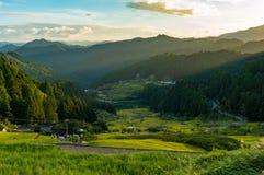 Puesta del sol sobre campo japonés con las montañas y los campos del arroz Fotografía de archivo