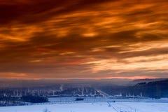 Puesta del sol sobre ciudad congelada Imagen de archivo libre de regalías