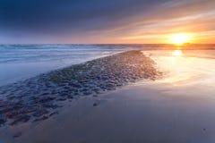 Puesta del sol sobre costa de Mar del Norte en Países Bajos Fotografía de archivo