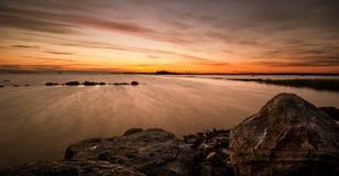 Puesta del sol sobre costa finlandesa Foto de archivo