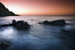 Puesta del sol sobre costa rocosa Imagen de archivo libre de regalías