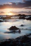 Puesta del sol sobre costa rocosa Fotografía de archivo libre de regalías