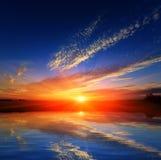 Puesta del sol sobre el agua Fotografía de archivo libre de regalías