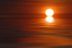 Puesta del sol sobre el agua Fotografía de archivo