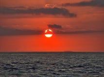 Puesta del sol sobre el agua Fotos de archivo libres de regalías