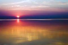 Puesta del sol sobre el agua Fotos de archivo