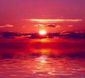 Puesta del sol sobre el agua Imagen de archivo libre de regalías