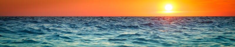Puesta del sol sobre el agua azul imagen de archivo