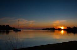 Puesta del sol sobre el agua con un velero Foto de archivo