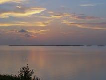 Puesta del sol sobre el agua en dominante largo Fotografía de archivo libre de regalías