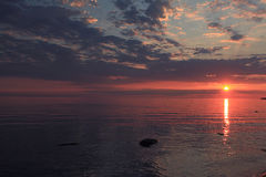 Puesta del sol sobre el agua tranquila del lago Foto de archivo libre de regalías