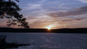 Puesta del sol sobre el agua y las montañas - timelapse 4K metrajes