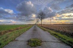 Puesta del sol sobre el camino del campo Imagen de archivo libre de regalías
