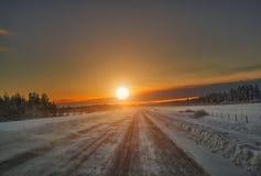 Puesta del sol sobre el camino, Laponia Finlandia Imagenes de archivo