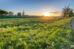 Puesta del sol sobre el campo cerca del pueblo Foto de archivo