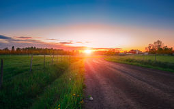 Puesta del sol sobre el campo verde Foto de archivo libre de regalías