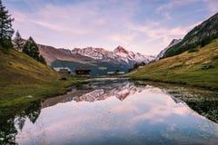 Puesta del sol sobre el chalet del montaña Nevado y madera que refleja en Altitu imágenes de archivo libres de regalías