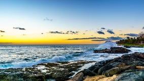 Puesta del sol sobre el horizonte con algunas nubes y las orillas rocosas de la costa oeste de Oahu Fotografía de archivo