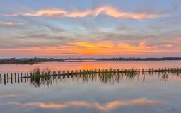 Puesta del sol sobre el lago con el riverbank campshedding imagen de archivo