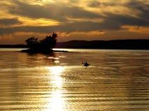 Puesta del sol sobre el lago con las fotos de la perfil-acción de la canoa Fotografía de archivo