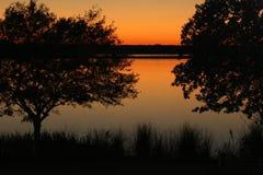 Puesta del sol sobre el lago con los árboles Foto de archivo