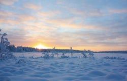 Puesta del sol sobre el lago del invierno Imagenes de archivo