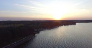 Puesta del sol sobre el lago en el bosque, cantidad aérea del abejón metrajes