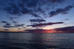 Puesta del sol sobre el lago en el cielo nublado de la primavera Foto de archivo