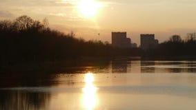 Puesta del sol sobre el lago en la ciudad almacen de video