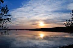 Puesta del sol sobre el lago en las maderas Fotos de archivo