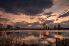 Puesta del sol sobre el lago tranquilo, reflexión del cielo en agua Foto de archivo