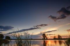Puesta del sol sobre el lago tranquilo, reflexión del cielo en agua Imagen de archivo