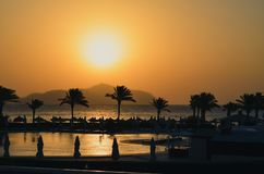 Puesta del sol sobre el mar con las montañas y las palmeras foto de archivo libre de regalías