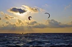 Puesta del sol sobre el mar con las personas que practica surf de la cometa Foto de archivo libre de regalías