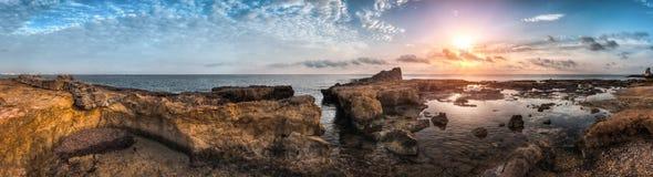 Puesta del sol sobre el mar y la costa rocosa Foto de archivo libre de regalías