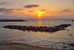Puesta del sol sobre el mar y la playa fotos de archivo